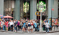 Crowds of visitors and natives wait to cross the street in front of a Starbucks in Times Square in New York, the Crossroads of the World, on Tuesday, August 21, 2012.  (© Richard B. Levine)