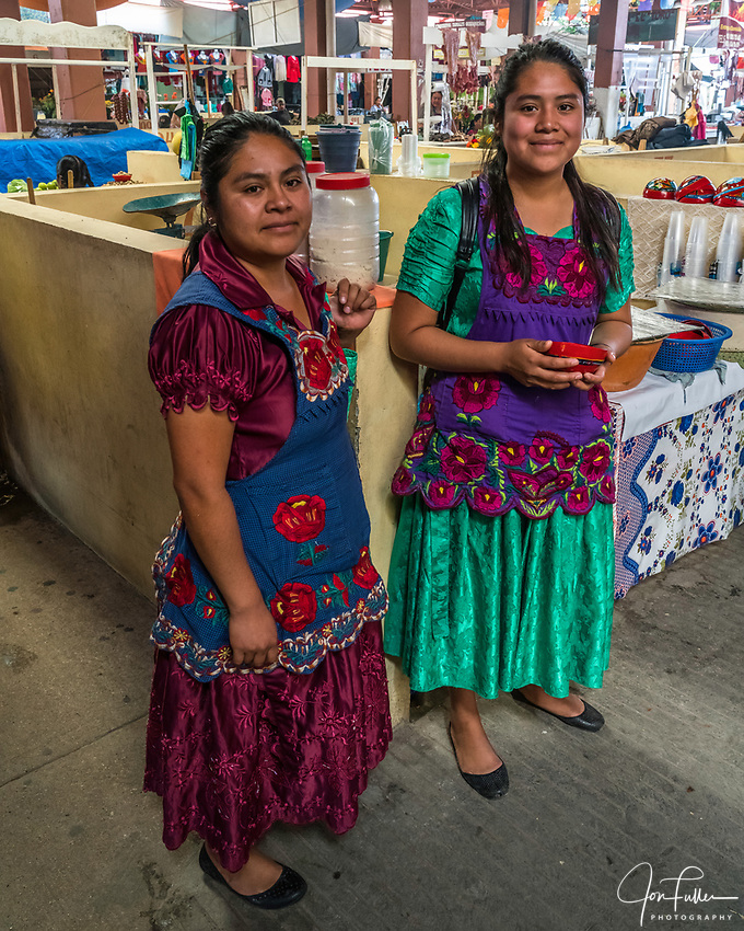 Two young Zapotec women from San Marcos Tlapazola in the market in Tlacolula in their traditional satin dresses and embroidered aprons, typical this town in the Central Valleys of Oaxaca, Mexico.