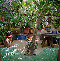 A shaded courtyard filled with plants is surrounded by a series of banquettes covered in ceramic tiles