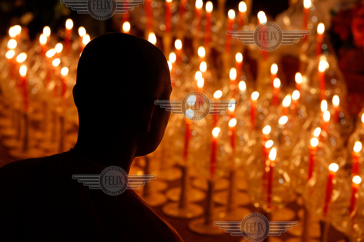 A monk stands in front of candles lit for Wesak (Buddha's birthday, awakening & nirvana) at the Grande Pagode de Vincennes.
