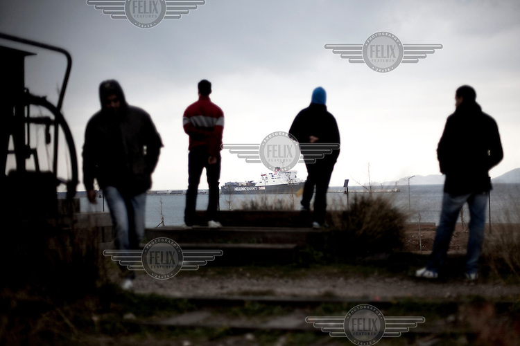 Greece / Korinth /Febr 20,2012. Immigrants close to the port of Korinth , thinking of the next day and how they will continue their journey to another European country.  Thousands of the immigrants in Greece gather in the country's biggest ports, in hopes of stowing away on one of the trucks loaded onto Italy-bound ships and ferries. Day and night, they sprint after the trucks as they pass through the gates, trying to latch onto the doors or crawl into the wheel wells. During the last years, in their effort to continue their journey, dozens have been found dead died suffocation inside the trucks.  Giorgos Moutafis