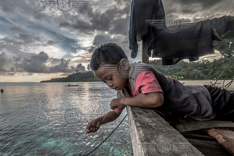 A Bajau boy fishes for reef fish with a hand line from the porch of his family's stilt home in the village of Pulo Papan.
