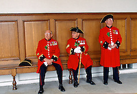 Chelsea Pensioners, dressed in their traditional uniform and red jacket and black tricorn hat, sitting inside the Royal Hospital in Chelsea during the Founder's Day Parade.