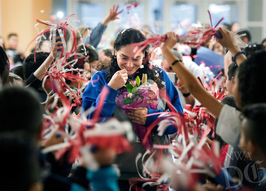 NWA Democrat-Gazette/BEN GOFF @NWABENGOFF<br /> Fifth grade students cheer while making a path for Beatriz Delgado as she arrives Friday, Feb. 16, 2018, during a surprise assembly at Old Wire Elementary in Rogers to congratulate her on achieving U.S. citizenship. Delgado began working at Old Wire Elementary as a crossing guard and has been the school's library aid for five years. Delgado, who lives nearby, has a child currently in the 4th grade at the school and two older children who previously attended. She has been an active member of the school's Parent-Teacher Organization and is described by school principal Shana Maxey as 'indispensable.' Delgado on Monday passed her U.S. citizenship test, and the school organized the patriotic assembly to congratulate her on the personal milestone.
