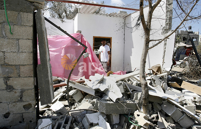 "A Palestinian man searches in a destroyed house in Khan Yunis in the southern Gaza Strip on September 11, 2014. Israel's deputy foreign minister,Tzahi Hanegbi , warned that Hamas was likely to resume ""violence"" if it feels it has made no political gains from upcoming talks in Cairo. Photo by Abed Rahim Khatib"