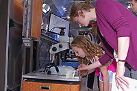 New York, NY, USA - October 8, 2017: BioBus II brings science to Pioneer Works Second Sunday event in Red Hook, Brooklyn. Scientist Mollie Thurman, and Sarah Weisberg use microscopes to show children and their parents the unseen world around them. www.biobus.org