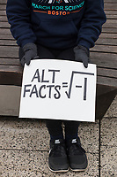"""Denise Gieseke, of Lincoln, Mass., holds a sign reading """"Alt Facts = [square root of negative one]"""" at the March for Science demonstration in Harvard University's Science Center Plaza in Cambridge, Massachusetts, on Sat., April 22, 2017. The square root of negative one is i, an imaginary number."""