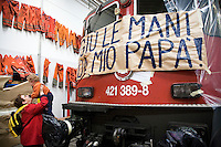 "Switzerland. Canton Ticino. Bellinzona. Officine FFS. Stabilimento Industriale SBB CFF FFS Cargo. Railway workers on strike. Building's occupation. A grandmother holds her grandson in her arms. Both came to support the boy's father who is on strike. A large sign is taped on the locomotive. "" Down your hands from my father"" . The father means the work. Leave the men to work so families can be happy. Orange clothes of the blue collar workers are hanged on the wall.  © 2008 Didier Ruef"