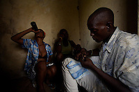 """Melvin, 29 yeas old prepares a marijuana cigarette while his two friends watch him   in an abandoned compound  in Monrovia, Liberia on  Wednesday March 21 2007..Melvin, 29 AKA """"Dad"""",  John, 29 AKA """"Desperate Soldier, Thomas 28 AKA """"Bullet Patrol"""", Leroy, 28, AKA """" Pussy Mechanic"""" and Steven 27 AKA """"Field Marshall"""" are all former child soldiers that found each other on the streets after the last round was fired in Liberia. Since then they """"Hustle"""" to put some food in their stomachs and buy some drugs to """" make them forget about their lives""""..ALL NAMES HAVE BEEN FICTIONALIZED TO PROTECT THE IDENTITIES OF THE 5 MEN."""