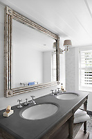 A mirror with tarnished silver paintwork hangs above the double basin in the ensuite bathroom