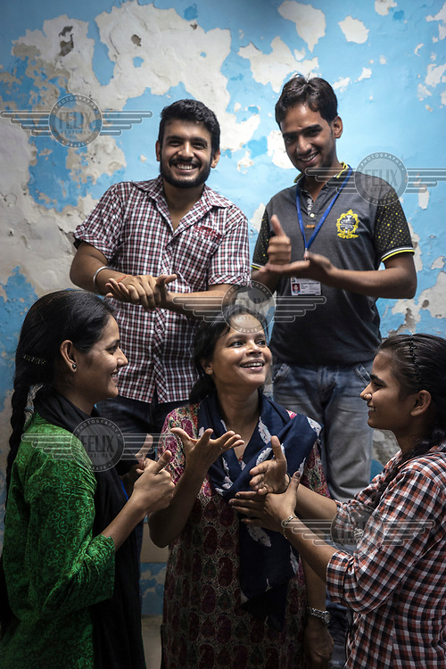 Runa Roka (54, centre), founder of the Noida Deaf Society, with her students in a classroom at the society's premises.<br /> <br /> <br /> The students are signing 'friend' (top left), 'help' (top right), 'appreciate' (bottom left) and 'share' (bottom right). While Runa signs 'happy'.
