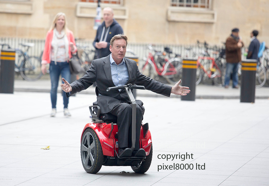 """Exclusive - pic shows: Frank Gardner BBC presenter disabled in terrorist shooting tries out a new """"segway wheelchair"""".<br /> <br /> It's called a Genny and costs £13,500 and does 14km/hour<br /> <br /> """"Look, mum, no hands"""" Gardner gets to grips with the balance of the device that was developed in partnership with Segway.<br /> <br /> It allows the new style wheelchair to turn on a sixpence without the need for using controls.  <br /> <br /> Frank was spotted testing the machine on the forecourt of the BBC HQ in London. He seemed a bit nervous at first with the idea that the two wheeler would balance itself.<br /> <br /> """"I'm just giving it a test run. It feels great but I'm still getting used to the idea.<br /> <br /> """"It certainly feels like it would be a lot of fun once you get the hang of it. I believe they do an off-road version as well which I would like to try.<br /> <br /> """"It feels strange that you can take you hands away and you fear that you will fall forwards of backwards. But off course you don't because of the gyroscope keeps you upright.""""<br /> <br /> Segway  have been around for years and it seems an obvious idea to incorporate the technology to a wheelchair. Why has no-one done this before?<br /> <br /> """"These new electric hover boards are cropping up everywhere nowadays. People using them on the pavements is technically illegal.<br /> <br /> """"But this device gets a special dispensation as it is a mobility device.""""<br /> <br /> Due to the elimination of the small wheels it is also much better on soft or rough terrain such as snow, gravel, sand or grass.<br /> <br /> Also according to the website it allows  you to hold hand with your nearest and dearest.<br /> <br /> <br /> <br /> <br /> <br /> <br /> <br /> <br /> <br /> Pic by Gavin Rodgers/Pixel 8000 Ltd"""