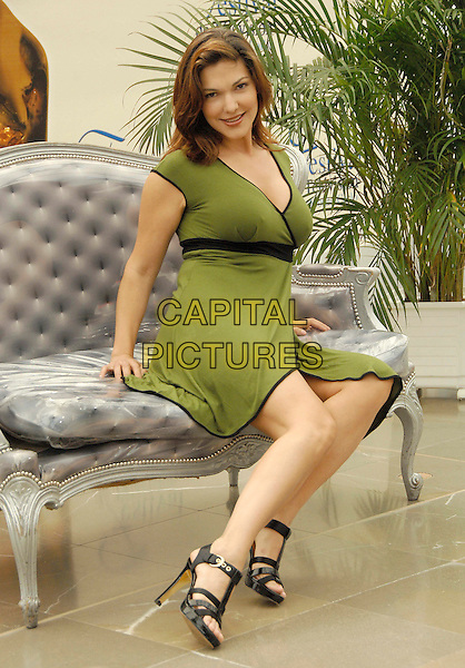 """LAURA HARRING.Photocall promoting the television series """"The Shield"""" during the fourth day of the 2008 Monte Carlo Television Festival held at Grimaldi Forum, Monaco, Principality of Monaco,.June 11th, 2008..full length green dress sitting black shoes strappy sandals.CAP/TTL .©TTL/Capital Pictures"""