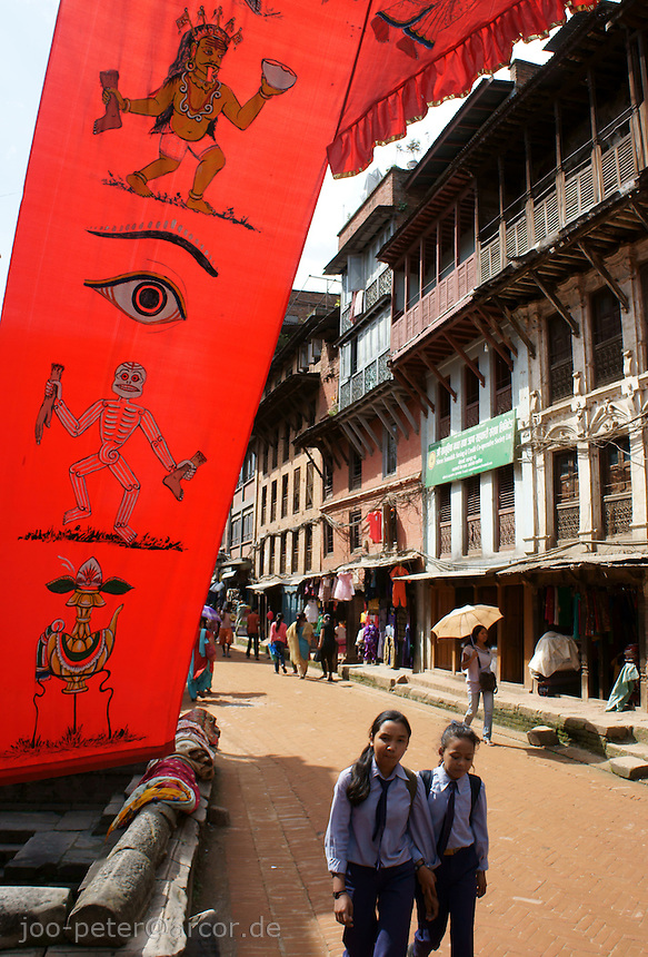 street scene in Bhaktapur Nepal with bloody red decoration banner  for Dashein festival time, showing a  sceleton and a an incarnation of Durga as man-eating fiercy goddess