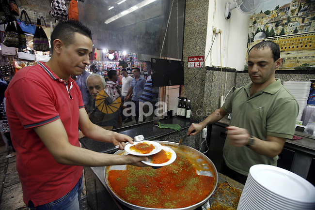 """A Palestinian vendor sells Konafa in his shop in Jerusalem's Old City on October 12, 2013 ahead of Muslim festival of Eid al-Adha, in preparation for Eid al-Adha. Millions of Muslims around the world celebrate Eid al-Adha or """"Feast of the Sacrifice"""", which marks the end of the annual hajj or pilgrimage to Mecca and celebrates Abraham's readiness to sacrifice his son to God. Photo by Saeed Qaq"""