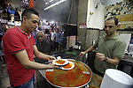 "A Palestinian vendor sells Konafa in his shop in Jerusalem's Old City on October 12, 2013 ahead of Muslim festival of Eid al-Adha, in preparation for Eid al-Adha. Millions of Muslims around the world celebrate Eid al-Adha or ""Feast of the Sacrifice"", which marks the end of the annual hajj or pilgrimage to Mecca and celebrates Abraham's readiness to sacrifice his son to God. Photo by Saeed Qaq"