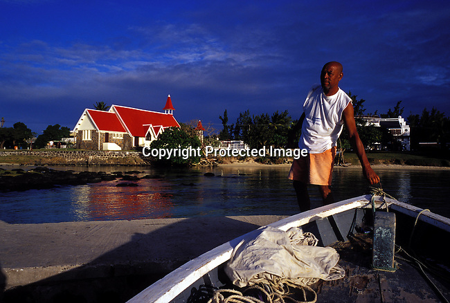 dicomau00020.Foreign Country. Mauritius. Noel Johnson, a fisherman arriving at shore with his boat in Cap Mahereux. In the background the Cap Mator Catholic church. Famous because of its red colored roof on July 4, 2003, on Mauritius. The island, located in the Indian Ocean, is a popular place for tourists. .©Per-Anders Pettersson/ iAfrika Photos