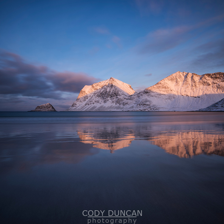 Winter sunrise illuminates mountains over Vik beach, Vestvågøy, Lofoten Islands, Norway