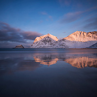 Winter sunrise illuminates mountains over Vik beach, Vestvågøy, Lofoten Islands, Norway