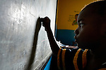 A girl writes on a blackboard during class in a day care center in Monrovia, Liberia, sponsored by United Methodist Women.