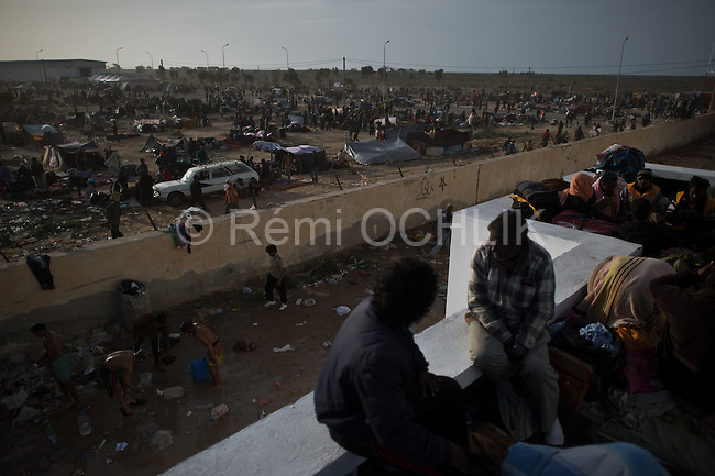 © Remi OCHLIK/IP3 -   RAS JEDIR, Tunisia 03 - Desperate refugees continued to flow Thursday to Libya's border with Tunisia, where thousands anxiously waited to be taken home and aid workers warned of a humanitarian disaster...Waves of refugees -- mainly migrant workers from countries such as Egypt and Bangladesh -- have been fleeing Libya as fighting rages between opponents and loyalists of strongman leader Moamer Kadhafi...At Tunisia's border post at Ras Jedir, a few Tunisian police officers and soldiers were struggling to contain thousands of new arrivals, baggage held over their heads, desperate to leave Libya.