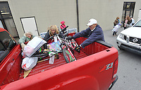 NWA Media/Michael Woods --12/17/2014-- w @NWAMICHAELW...Volunteers (left to right) Debby Stumbaugh, Payton Stumbaugh, and Delano Cotton, help load up a truck with toys and food Wednesday morning at the Salvation Army building in Springdale.  Several volunteers helped distribute toys and food to local families for the holidays.