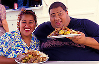 Lina Girl and Bruddah Sam, hosts of the now defunct cable show ìLocal Kine Grindsî, holding plate lunches purchased at the lunch wagon behind them