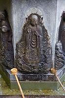 Kyoto City, Japan<br /> Adashino Nenbutsu-ji Temple, bamboo dippers resting on a stone chuzua (ritual washing trough) with Buddha figures