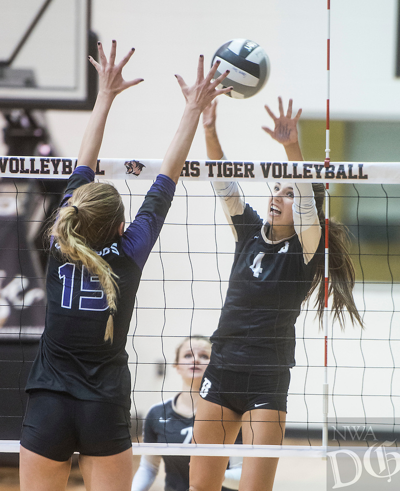 NWA Democrat-Gazette/ANTHONY REYES &bull; @NWATONYR<br /> Sadie Pate (4) of Bentonville spikes the ball against Ella May Powell (15) of Fayetteville Tuesday, Oct. 20, 2015 at Tiger Arena in Bentonville. The Lady Bulldogs won 3-1 going undefeated in 7A conference play.
