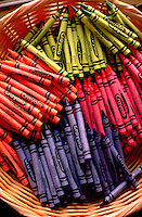 Various colored crayons neatly organized in wicker basket.  St Paul  Minnesota USA
