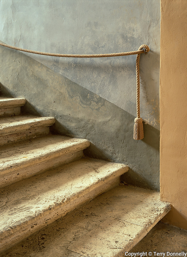 San Quirico d'Orcia, Tuscany, Itlay,<br /> Soft light streaming into a stairwell with a tasseled rope railing in the Palazzo Pubblico