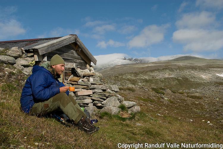 Mann slapper av i sola utenfor steinbu i Svånådalen i Dovrefjell  ---- Man relaxing outside hut in Svånådalen in Dovrefjell
