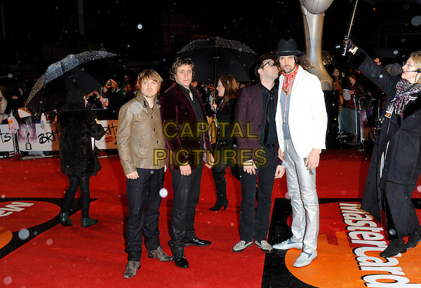 KASABIAN - Ian Matthews, Chris Edwards, Tom Meighan & Sergio Pizzorno.At the Brit Awards 2010 held at Earls Court, London, England, UK,.February 16th 2010.Brits arrivals full length band group black hat white suit jacket red scarf maroon blazer tie shirt glasses velvet  umbrellas .CAP/FIN.©Steve Finn/Capital Pictures.