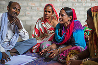 Jeevika's Field Associate, Jagganath Prasad (extreme left), listens as women vegetable farmers have a discussion during a Producer Group meeting in Machahi village, Muzaffarpur, Bihar, India on October 26th, 2016. Non-profit organisation Technoserve works with women vegetable farmers in Muzaffarpur, providing technical support in forward linkage, streamlining their business models and linking them directly to an international market through Electronic Trading Platforms. Photograph by Suzanne Lee for Technoserve