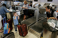 Alaska Airlines customer service agent Cheryl Canchola, right, speaks with Jaxon Mayer,4, of Arlington, as his parents, Jennifer and John Mayer check their bags for a trip to Disneyland using the new system at Sea-Tac Airport on October 16, 2007. Hollis Lovelace (cq), rear, helps the Mayer family. The new system replaces the traditional ticket counter with islands. Photo by Meryl Schenker/Seattle Post-Intelligencer