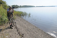 NWA Democrat-Gazette/FLIP PUTTHOFF <br /> Joe Neal of Fayetteville peers through a spotting scope Sept. 16 2016 at birds along the Arkansas River near Alma. Neal has a birding trail he follows in the river valley, making several stops to see birds on land and water.