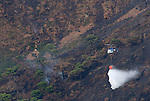 Twin Rotor Kamov helicopter dropping water on mountain side fire. Los Reales mountain, Estepona, Andalucia,Spain.