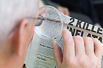 A Man reading a newspaper with a magnifying glass at the Nottingham Royal Society for the Blind ,NRSB,. MR
