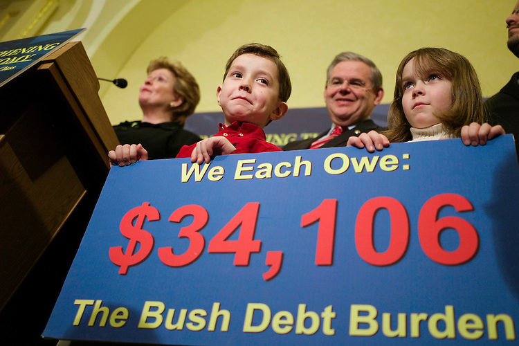 WASHINGTON, DC - Feb. 12: William Thorne, 5, and sister Caroline, 6, hold a sign during a news conference with Senate Budget Chairman Kent Conrad, D-N.D., Senate Democrat Steering & Outreach Committee Chairwoman Debbie Stabenow, D-Mich., speaking, and Sen. Robert Menendez, D-N.J., behind the children, on the impact of the president's proposed budget. Cecily Thorne of Silver Spring, Md., the children's mother, said they are related to a member of Conrad's staff. (Photo by Scott J. Ferrell/Congressional Quarterly)