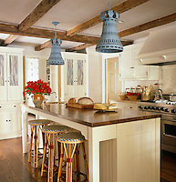A pair of blue/grey pendant lights above the large wood-topped kitchen island