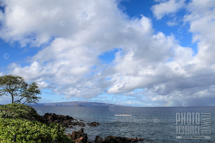 Paddlers in an outrigger canoe journey beyond a snippet of rainbow in waters off of Wailea Beach, South Maui.