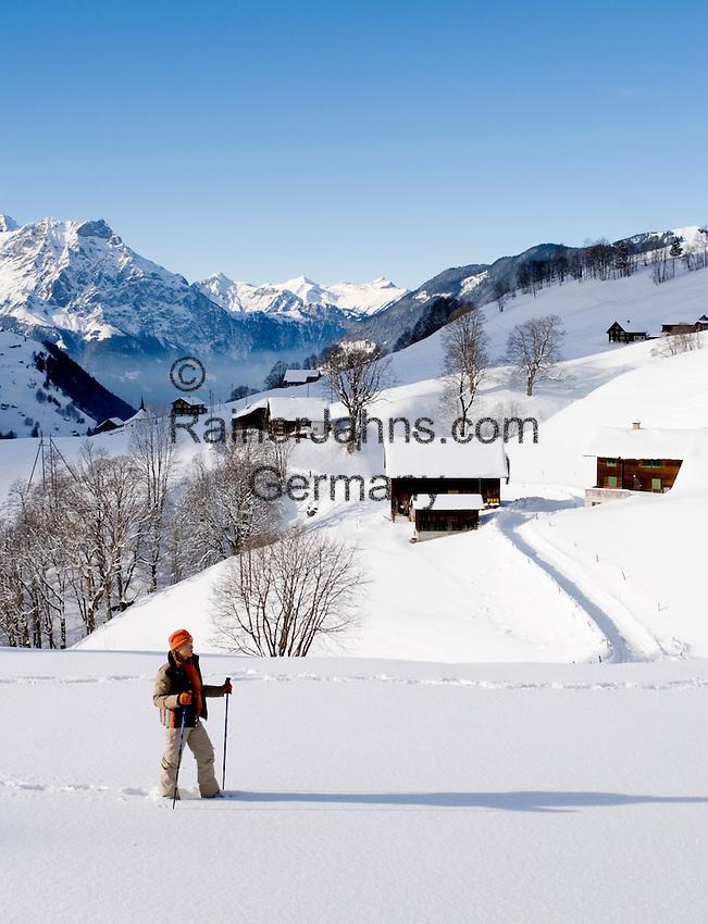 Switzerland, Canton Uri, Urigen: mountain village at Schaechen Valley and Swiss Central Alps - woman hiking in deep snow