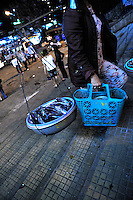 Unlicensed street hawkers have to keep on the move to avoid the police. Here a woman selling fresh fish and cooked food hurries up steps away from main market area. Da Lat, Vietnam