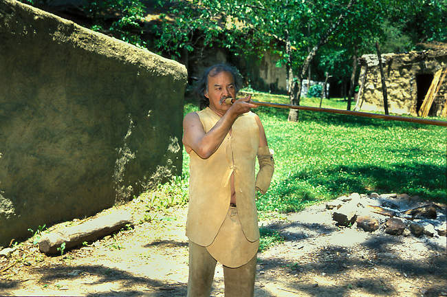 Cherokee man dressed in traditional deerskin clothing demonstrates a blow gun made from river cane at the Cherokee Indian Village in Tahlequah OK.