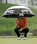 SUZHOU, CHINA - APRIL 18:  Rhys Davies of Wales shelters from the rain under his umbrella on the 6th green during the Round Four of the Volvo China Open on April 18, 2010 in Suzhou, China. Photo by Victor Fraile / The Power of Sport Images