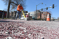 NWA Democrat-Gazette/J.T. WAMPLER Terry Weaver, traffic technician for the Fayetteville Transportation Division, uses a grinder Monday March 18, 2019 to remove material from a crosswalk at Dickson Street and Arkansas Ave. The crosswalks were recently redone but delays caused the material used for the project to expire and not adhere properly. Replacement material should be covered by the manufacturer's warranty.