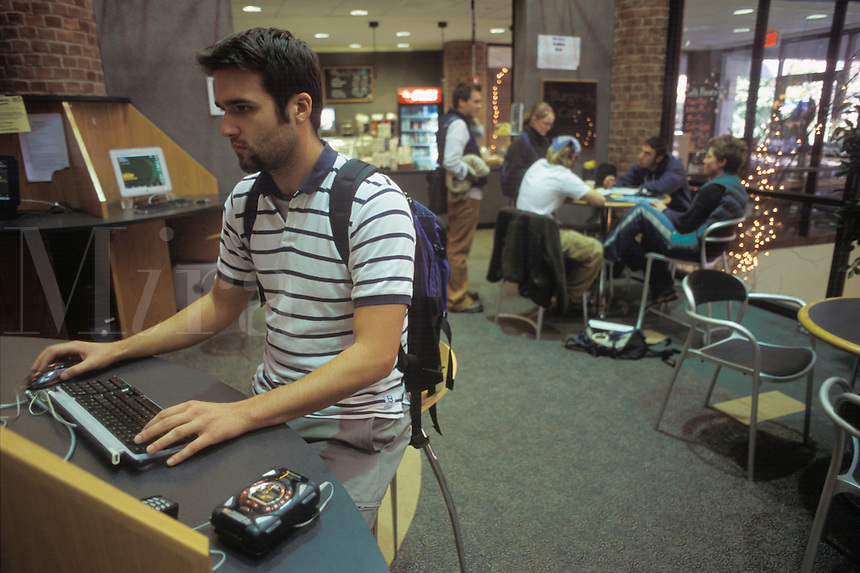 College students in student center, one on the Internet, others socializing.