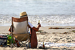 Man in folding chair relaxes with a cold beer on the beach