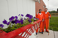 Samuel Soto and Shawn O'Hanlon pose by a flower box that the inmate built. The petunias in the box are growing in compost from the Philadelphia Prisons Composting Program.