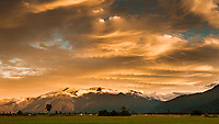 Dramatic sunset over farmland near Whataroa. Southern Alps with Mt. Adams in background,  West Coast, New Zealand, NZ